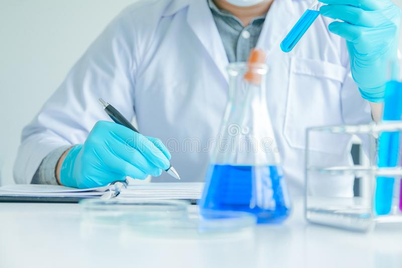 Medical science or male Compiling an Analysis Report in laboratory room research performs tests with blue liquid on test tube, stock photo