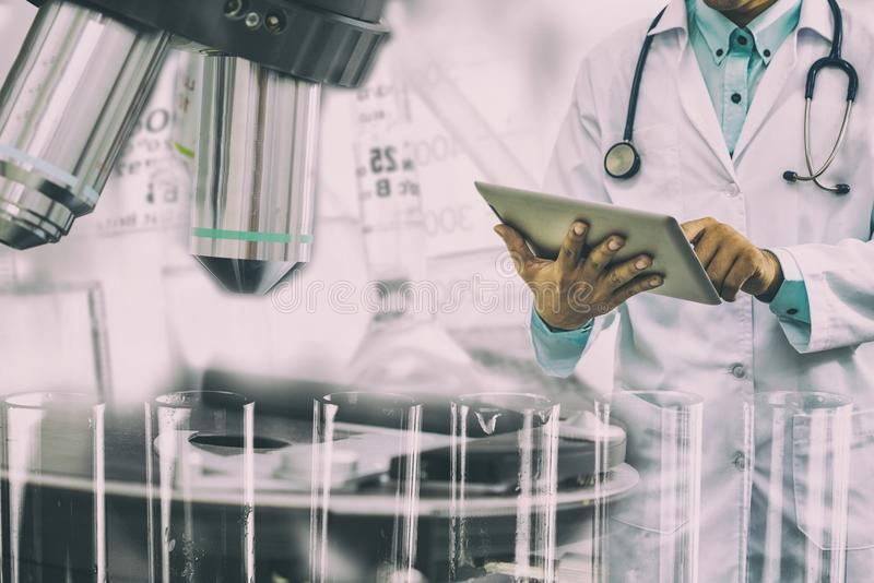 Medical science research concept. Medical science research and development concept - Doctor holding tablet computer with scientific instrument, microscope and royalty free stock photo
