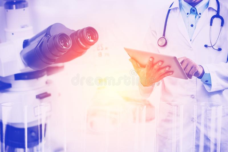 Medical science research concept. Medical science research and development concept - Doctor holding tablet computer with scientific instrument, microscope and stock images