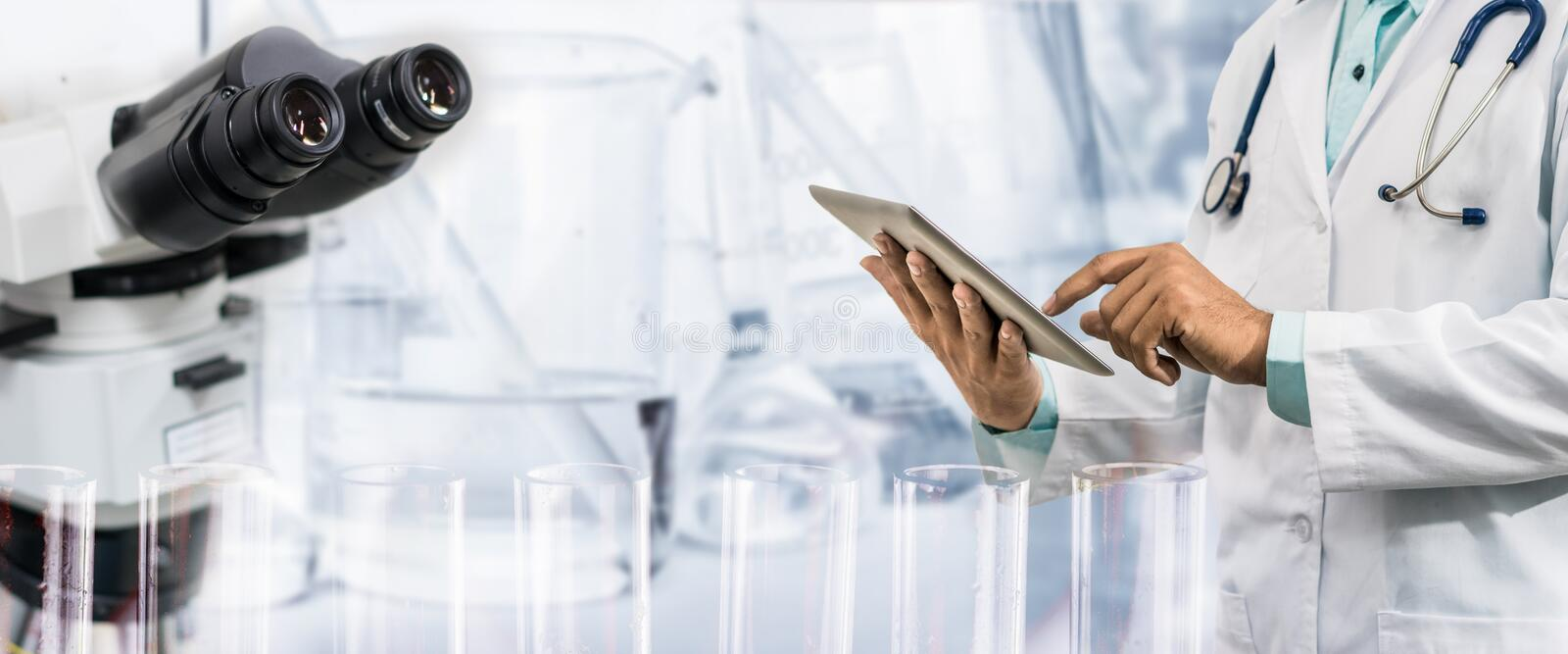 Medical science research concept. Medical science research and development concept - Doctor holding tablet computer with scientific instrument, microscope and royalty free stock photography