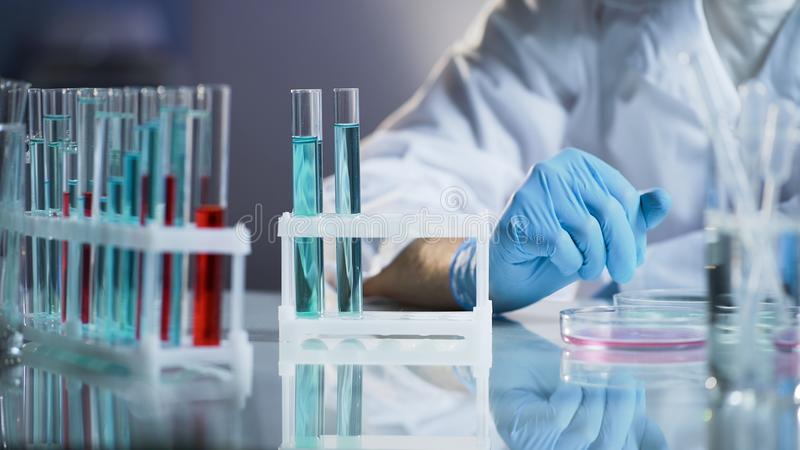 Medical scientist conducting test, observing reactions in glass flasks, research. Stock video royalty free stock photos