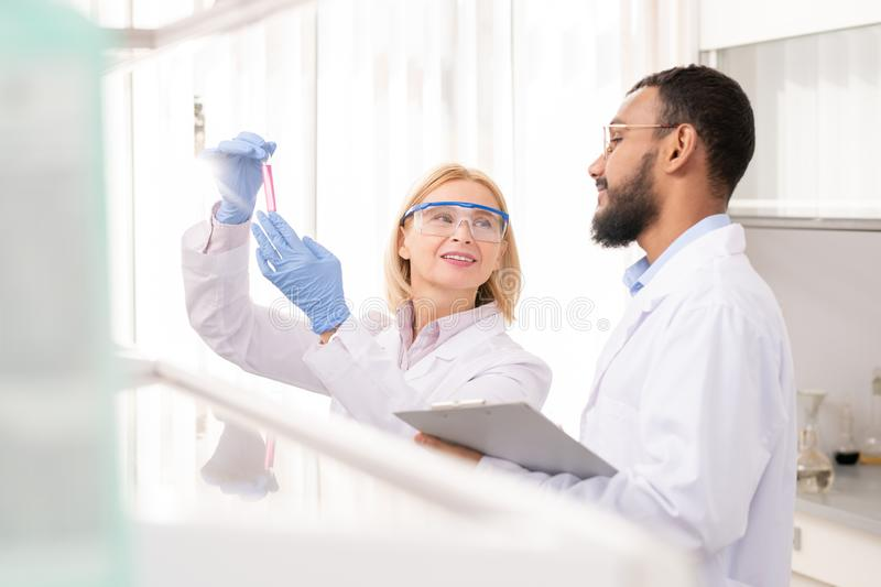 Medical scientists satisfied with result of experiment. Positive confident medical scientists in lab coats satisfied with result of experiment examining liquid royalty free stock images