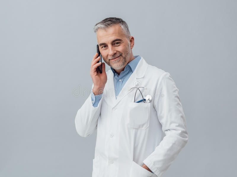 Medical service consultation by phone. Confident mature doctor having a phone call with his smartphone: medical service consultation by phone royalty free stock images