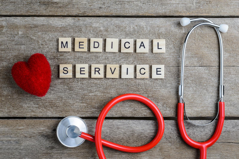 Medical Service text word made with wood blocks and Red Heart,stethoscope on wooden table stock image