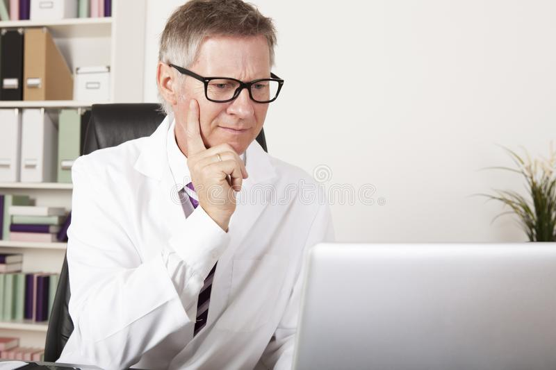 Medical Specialist Seriously Reading at Computer. Medical Specialist Seriously Reading Diagnosis Reports at Computer royalty free stock image