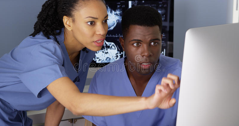 Medical specialist working with colleague on computer stock photos