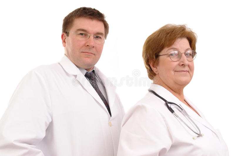 Medical staff. Young male and senior female doctors posing side by side over white background stock photos