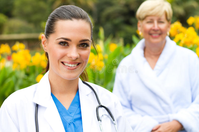 Medical staff. Young happy female medical staff and senior female patient stock photo