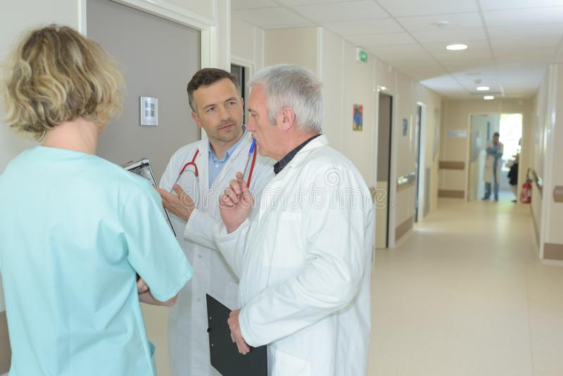 Medical staff conferring in hospital corridor stock photography