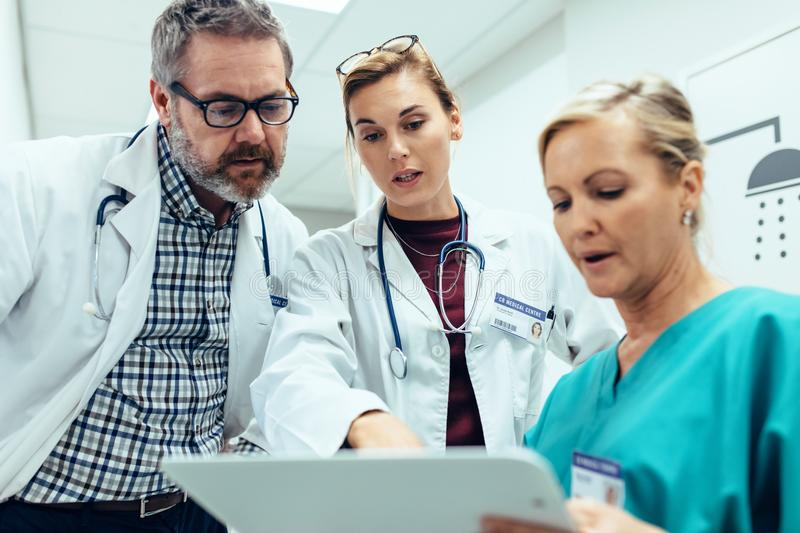 Medical staff discussing over medical reports in hospital. Medical staff discussing over medical reports. Healthcare professionals having discussion in hospital stock photos