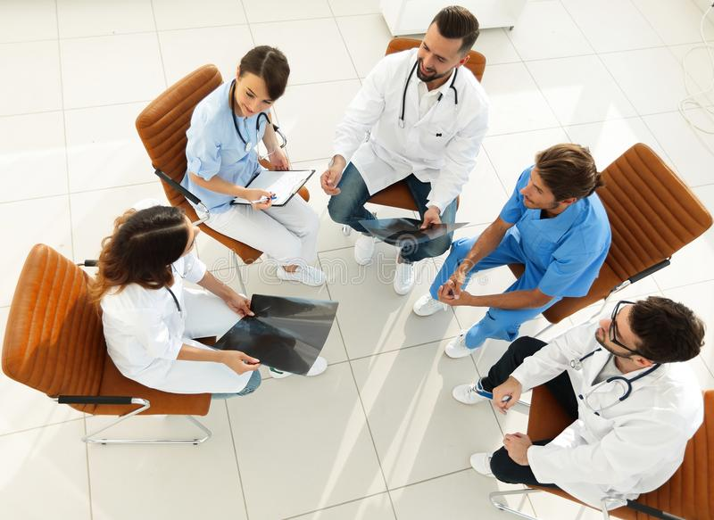 Medical staff ,discussing the work plan with the patients. Sitting in the office stock photography