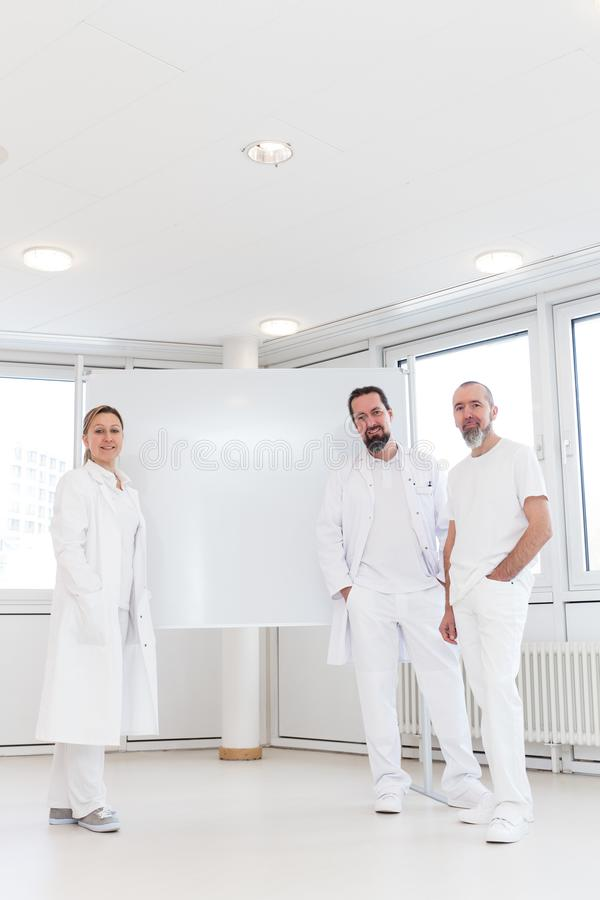 Medical staff in front of an empty whiteboard. Lot of copyspace with medic professionals royalty free stock photo