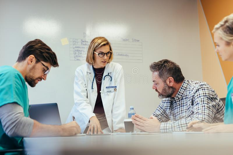 Medical staff having conference meeting in hospital. Female leadership. Medical staff having conference meeting in hospital. Female doctor briefing hospital royalty free stock photos