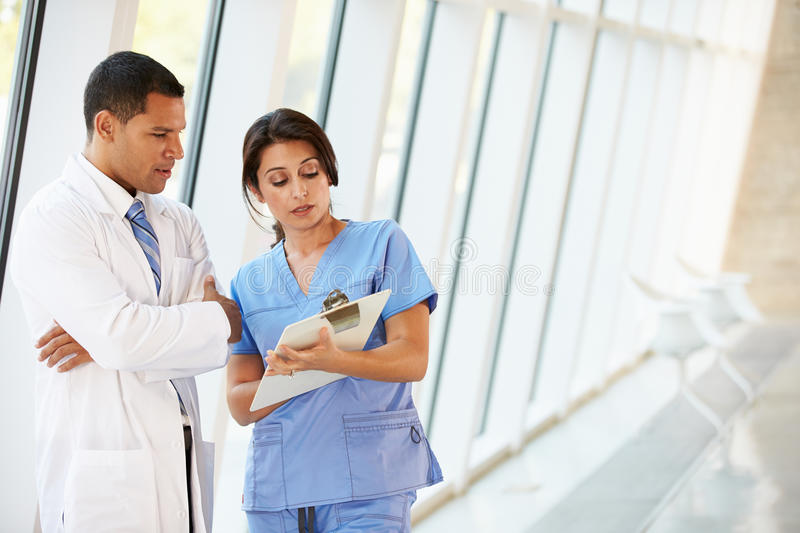 Medical Staff Having Discussion In Modern Hospital Corridor. Concentrating royalty free stock images