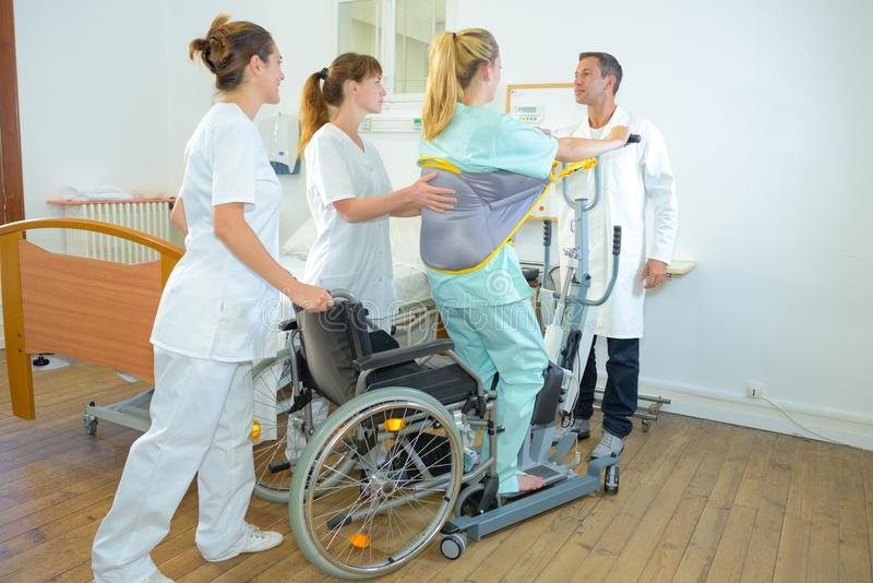 Medical staff helping woman to standing. Medical staff helping women to standing woman stock image