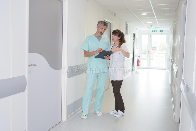 Medical staff looking at clipboard in hospital corridor royalty free stock image