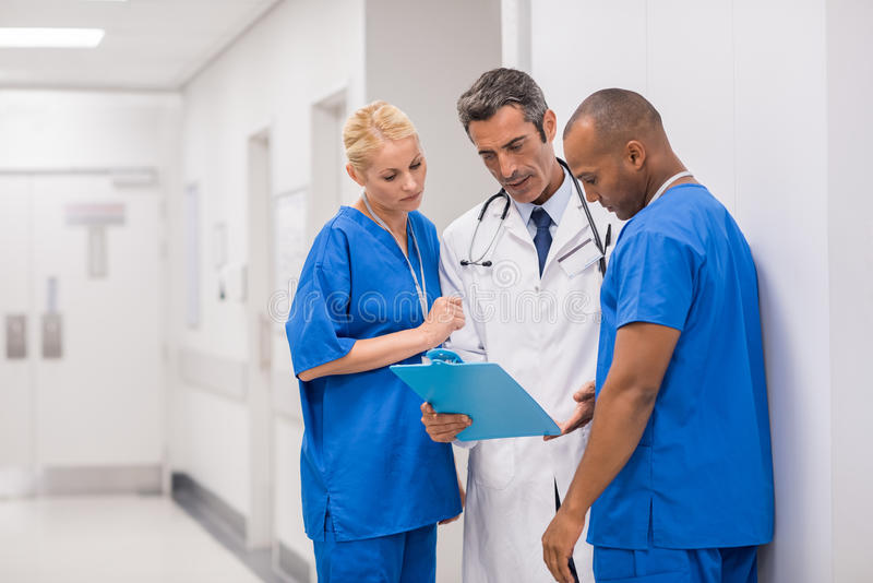 Medical staff meeting. Medical staff having discussion in modern hospital hallway. Mature doctor and multiethnic surgeon talking in the corridor and looking at royalty free stock photography