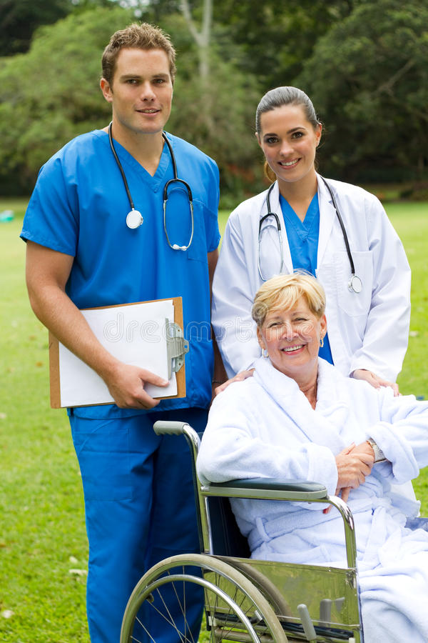 Medical staff and patient. Young medical staff and senior patient in hospital garden stock image