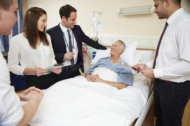 Medical Staff On Rounds Standing By Male Patient's Bed royalty free stock photo