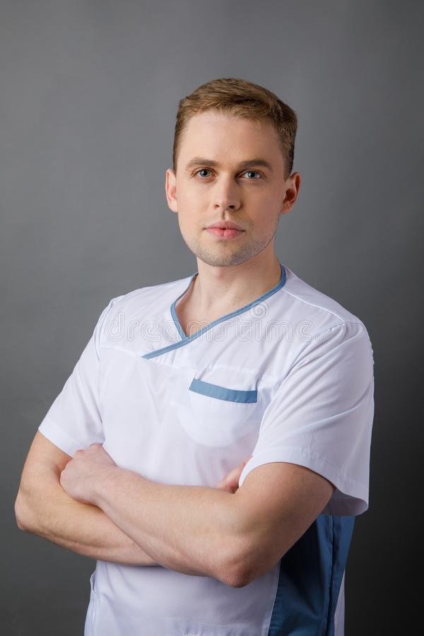 Medical staff. Young sympathetic doctor stands isolated on a grey background dressed in a uniform for doctors stock photos