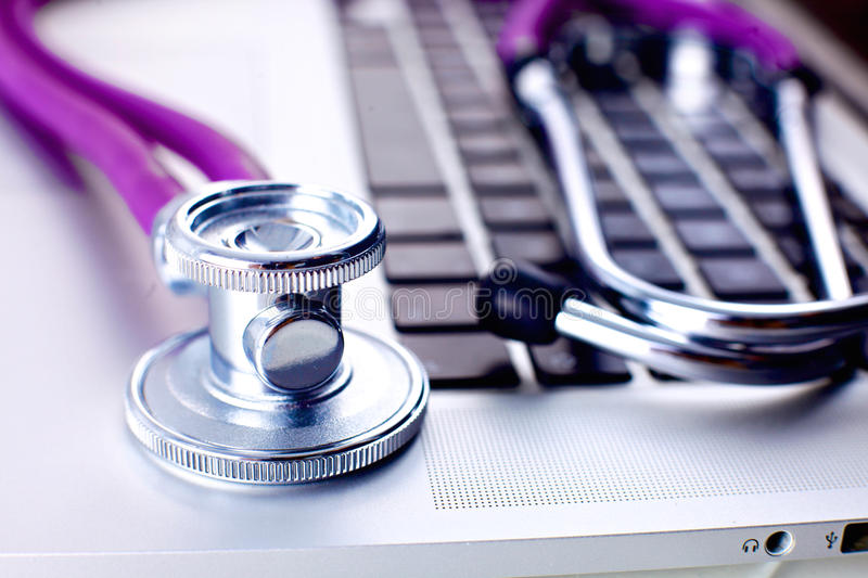 Medical stethoscope lying on a computer keyboard royalty free stock photos