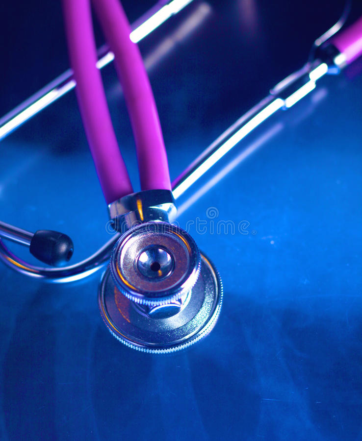 Medical stethoscope lying on an x-ray. Medical violet stethoscope lying in white background stock images