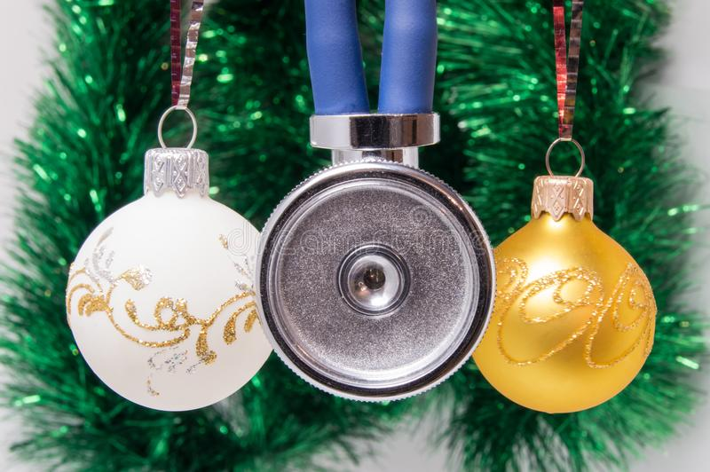 Medical stethoscope membrane anteriorly with two tubes surrounded by Christmas tree balls on blurred background with adornment. Co royalty free stock image