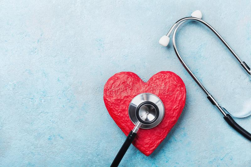 Medical stethoscope and red heart on blue background top view. Healthcare, pulse, heartbeat, medicare and cardiology concept. stock photography
