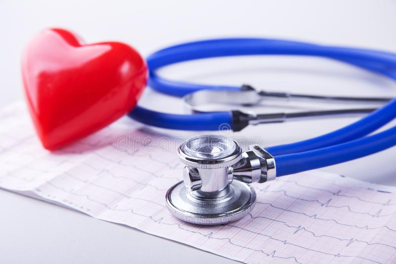 Medical stethoscope and red heart lying on cardiogram chart closeup. Medical help, prophylaxis, disease prevention or stock photos