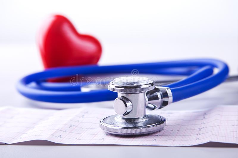 Medical stethoscope and red heart lying on cardiogram chart closeup. Medical help, prophylaxis, disease prevention or royalty free stock images