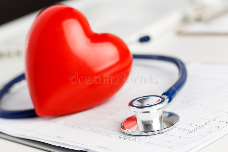 Medical stethoscope and red toy heart lying on cardiogram chart stock photography