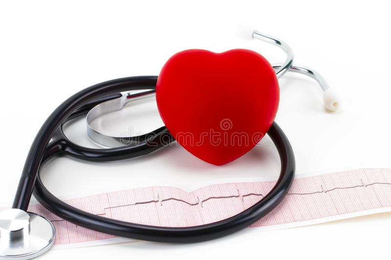 Medical stethoscope and red toy heart lying on cardiogram chart royalty free stock image