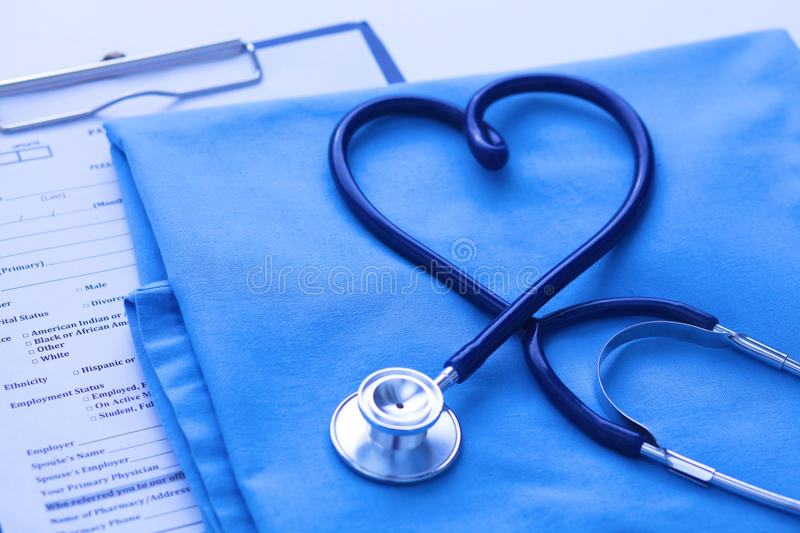 Medical stethoscope twisted in heart shape lying on patient medical history list and blue doctor uniform closeup. Medical help or insurance concept. Cardiology stock photos