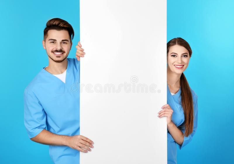 Medical students with blank poster on color background. Space for text royalty free stock image