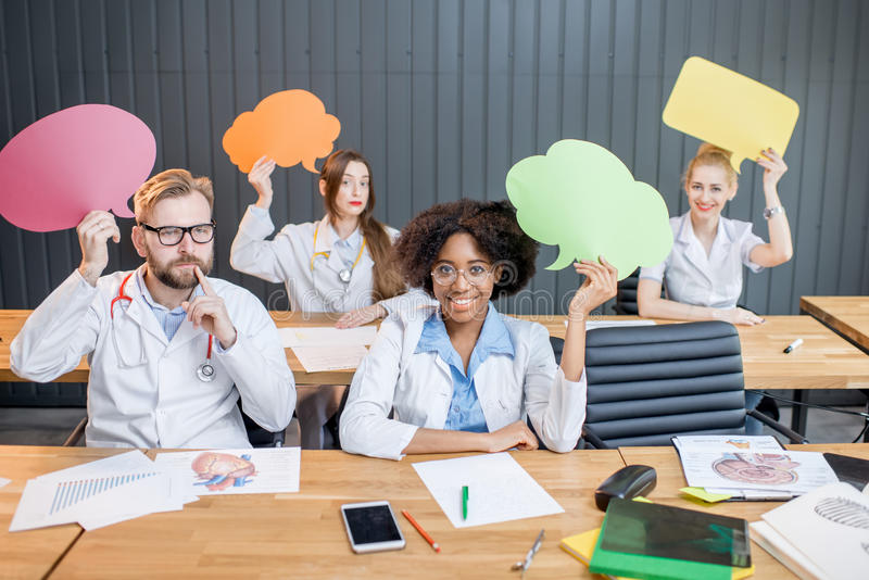 Medical students at the classroom. Medical students holding paper clouds sitting during the lesson at the classroom royalty free stock photography