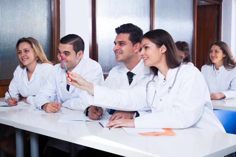Medical students sitting in audience. Medical students sitting in the audience listening to teacher stock image
