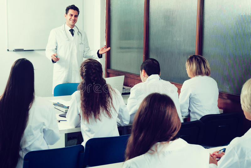 Medical students sitting in audience. Medical students sitting in the audience listening to teacher royalty free stock photography