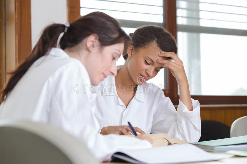 Medical students sitting and talking at university. Medical students sitting and talking at the university stock images
