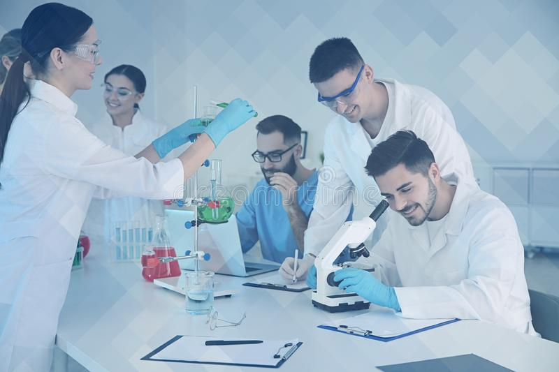 Medical students working in scientific laboratory, color tone. Medical students working in modern scientific laboratory, color tone stock images