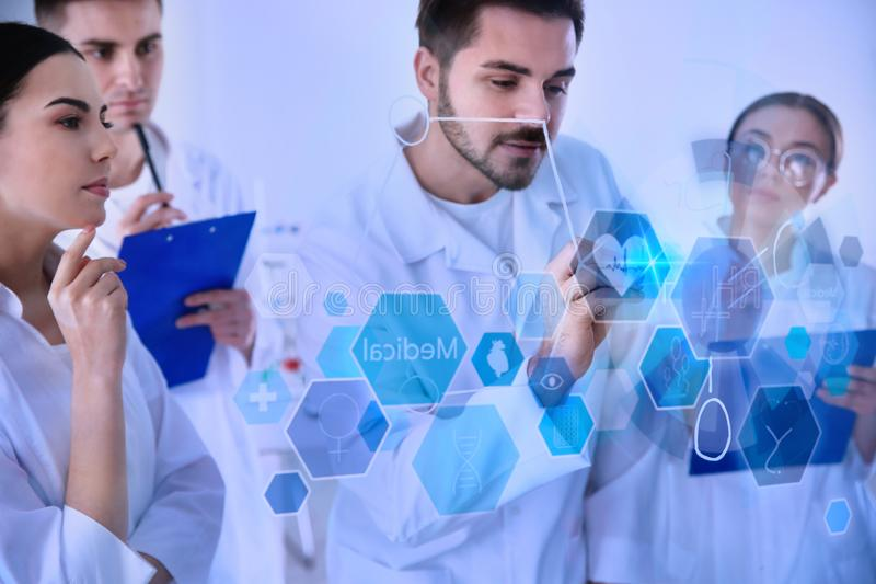 Medical students working with virtual screen in laboratory. Color tone royalty free stock photo