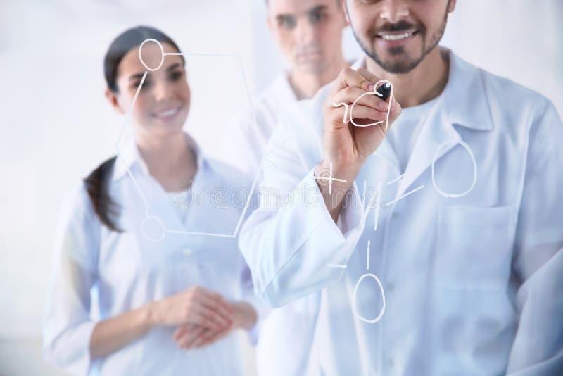 Medical students writing chemical formula on glass in laboratory. Medical students writing chemical formula on glass whiteboard in laboratory royalty free stock photos