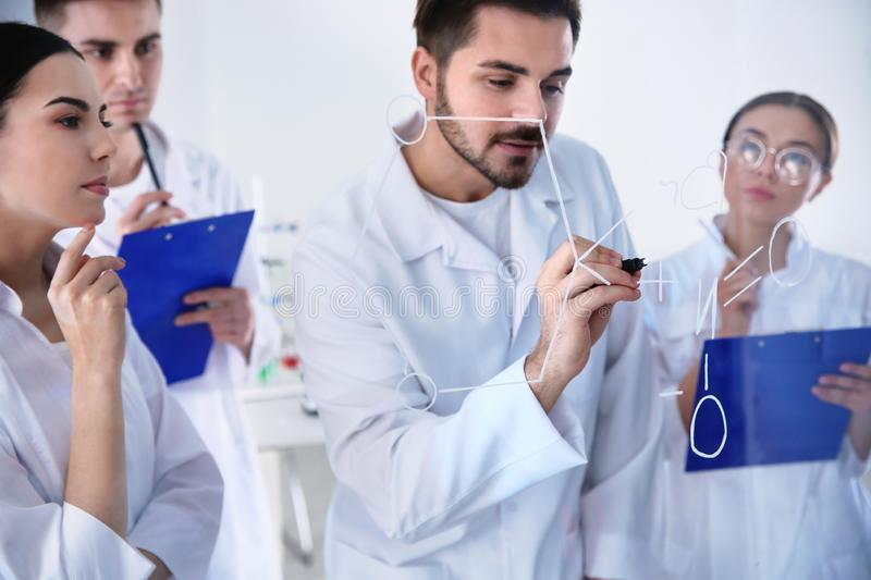 Medical students writing chemical formula on glass whiteboard. In laboratory stock photos