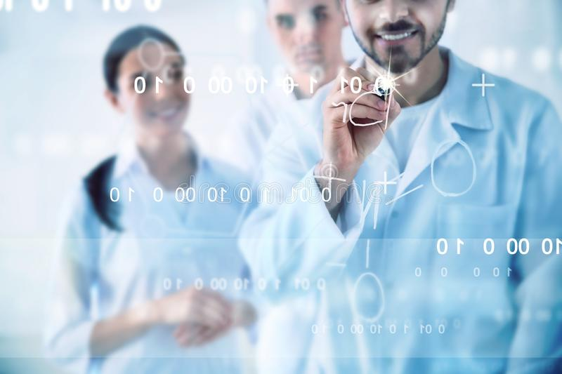 Medical students writing chemical formula on virtual screen. In laboratory stock photography