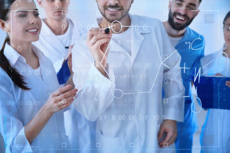 Medical students writing chemical formula on virtual screen. In laboratory stock image