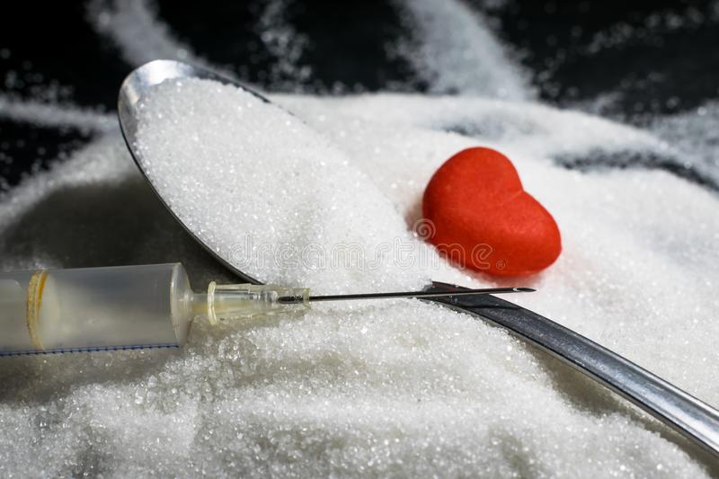 Medical syringe, pile of sugar grain with spoon and heart in background, insulin shot and diabetes concept royalty free stock photos