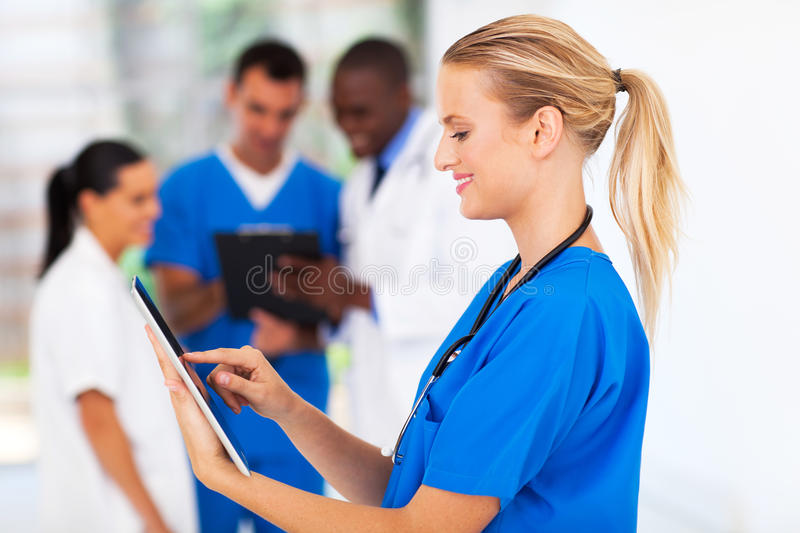 Medical tablet computer. Attractive young medical nurse using tablet computer stock images