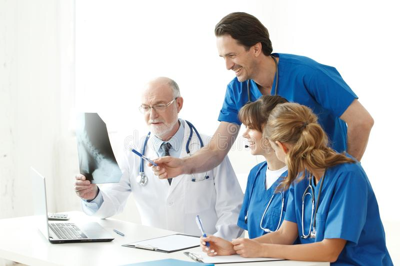 Medical team checking X-ray results. Medical team checking on X-ray results isolated on white royalty free stock photos