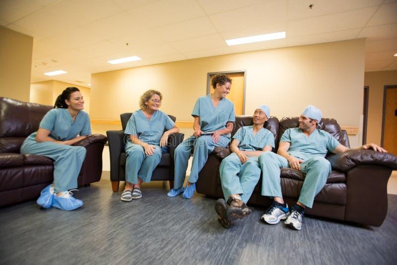 Medical Team Conversing In Hospital's Waiting Room. Full length of multiethnic medical team conversing in hospital's waiting room royalty free stock image