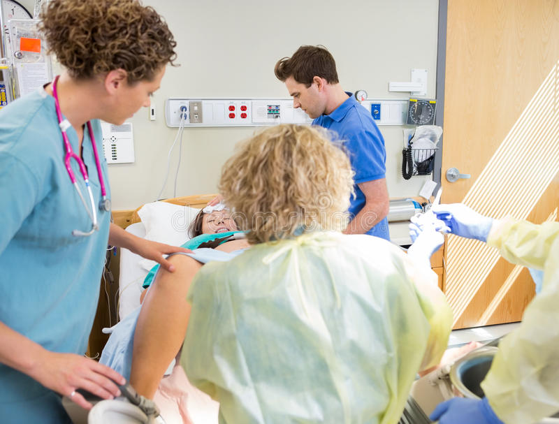 Medical Team Delivering Baby. In hospital with hsuband comforting wife stock photography