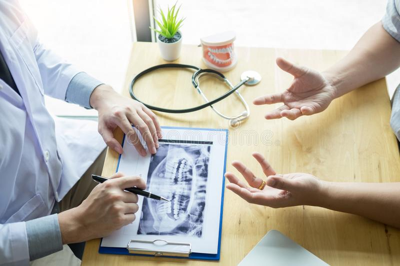 Medical team discussing, health care talking to female patient, Medical conferrence concept, doctor holding and looking at dental. X-ray attending a client royalty free stock photo